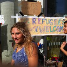"""Schülerin am Bahnhof vor Plakat """"Refugees welcome"""""""
