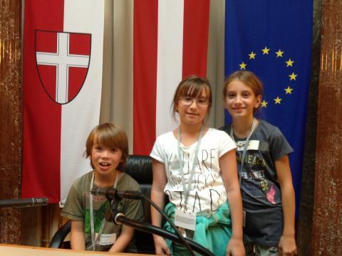 drei Schülerinnen vor der Wien-, Österreich- und Europaflagge