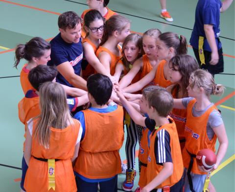 Mannschaft steht im Kreis beisammen legen ihre Hände in der Mitte zusammen zum Gruß