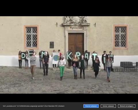 Schülergruppe mit Buchstabentafeln und Masken