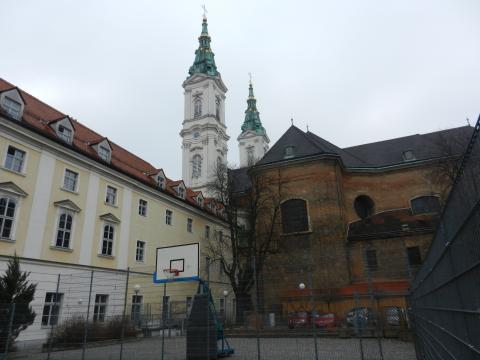 Hartplatz mit Basketballkorb und Kirchturm im Hintergrund
