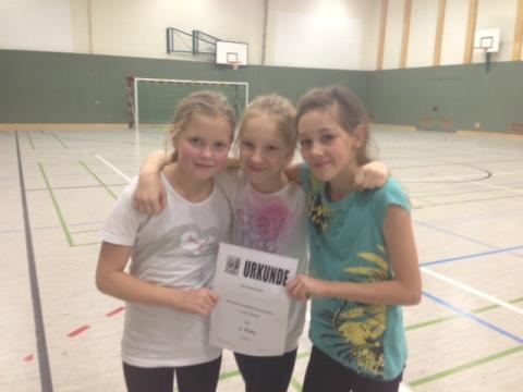 drei Fußballerinnen mit Urkunde