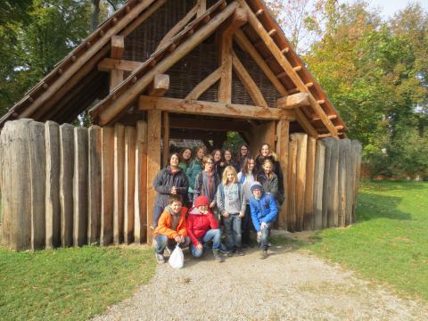 Schülergruppe vor steinzeitlichem Holzhaus