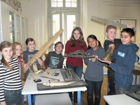 Kinder mit den Exponaten der Biologiesammlung