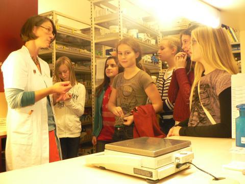 Apothekerin und Schülerinnen mit einer Waage
